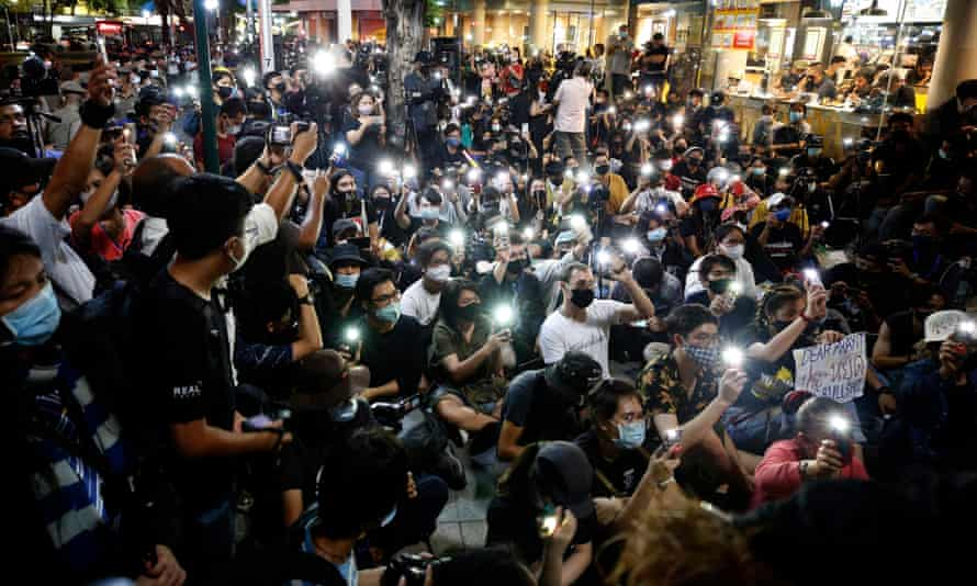 Thai students and pro-democracy activists activate torches on their phones during the rally in Bangkok.