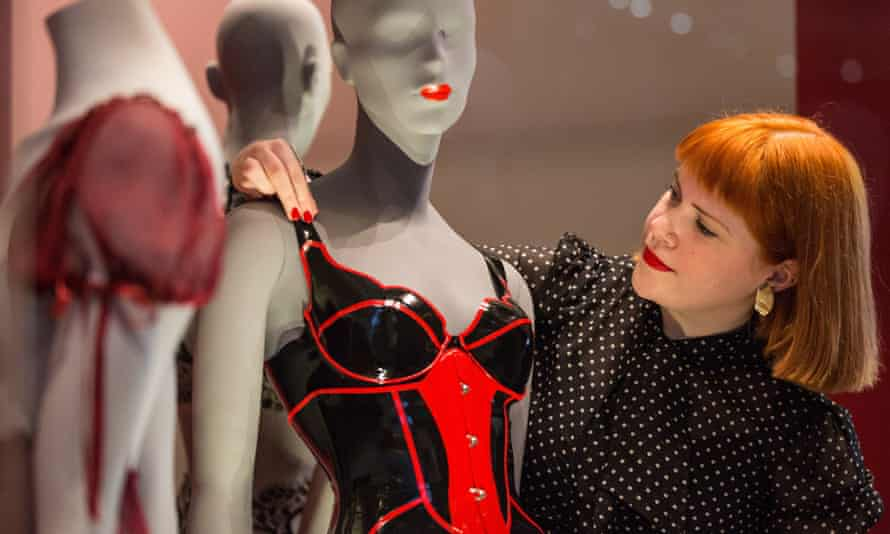 A museum worker adjusts a black and red shiny corset in a display case