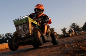 The mower of the Who's Racing team takes a corner as the sun rises.