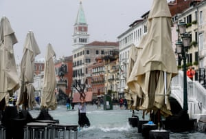 A man carries a table in the flooded Riva degli Schiavoni during a high-water (Acqua Alta) alert in Venice