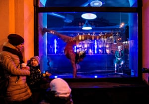 People watch a performance by members of the new circus company Cirk La Putyka in a pub window in Prague.