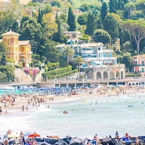 """The beach and sea at Levanto, Italy, on a bright, sunny day.  """"I'm always looking for the idyllic Italian beach. I went to Levanto in Liguria with little expectation, and was blown away by the kaleidoscopic colours of the beach umbrellas and the crowds surrounded by lush mountains and traditional architecture."""""""
