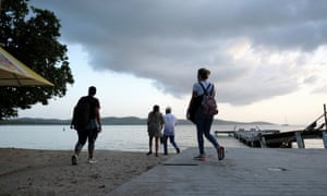 People walk on the beach in the tourist zone of Boqueron as Tropical Storm Dorian approaches in Cabo Rojo, Puerto Rico Monday.