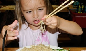 Child eating noodles with chopsticks in a restaurant