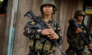 Philippines army soldiers patrol as government forces continue their assault against insurgents