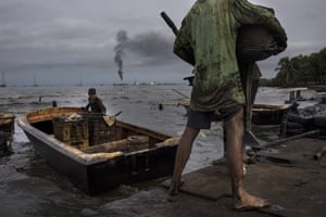 Fishermen covered in oil get their boat ready for fishing on Venezuela's Lake Maracaibo, a view of La Salina crude oil shipping terminal in the distance