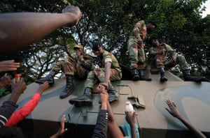 Civilians celebrate with members of the armed forces on the streets of Harare