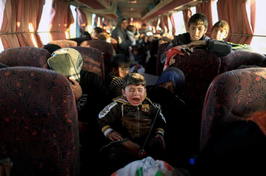 A boy who fled a village controlled by Isis cries as he sits with his family on a bus heading to a camp in Hammam al-Alil, south of Mosul, Iraq, on 22 February