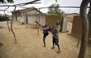 Children play with a ball made from plastic bags in the street outside their houses in the village of Mbyo, near Nyamata.