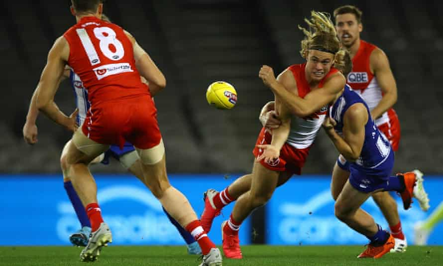 The Swans' James Rowbottom handballs during the match between North Melbourne and Sydney