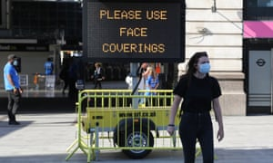 A woman walks passed a sign advising people to wear face coverings outside Victoria station in central London