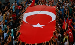People gather at a pro-government rally with large Turkish flag