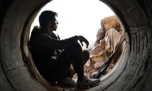 A rebel fighter rests in a pipe in Homs