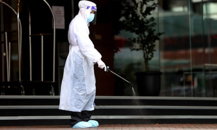 A hotel worker sanitises the outside of Stamford Plaza in Auckland, New Zealand, one of the country's coronavirus quarantine facilities. The 30 deportees from Australia will be held at a secret isolation site.