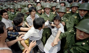 A young woman is caught between civilians and Chinese soldiers near the Great Hall of the People in Beijing on 3 June 1989.