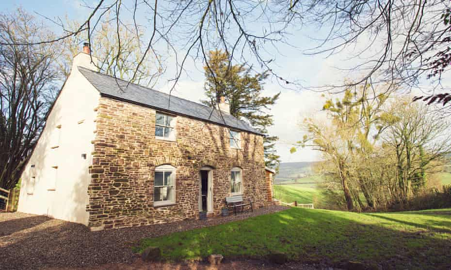 The stone Fox & Hounds Cottage, in spring sunshine, with hills and countryside in the background –  Monmouthshire, Wales