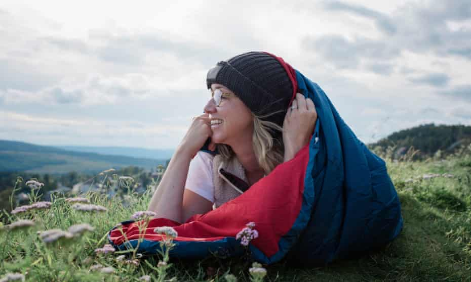 Woman laying in sleeping bag on a mountain looking at the view smiling.