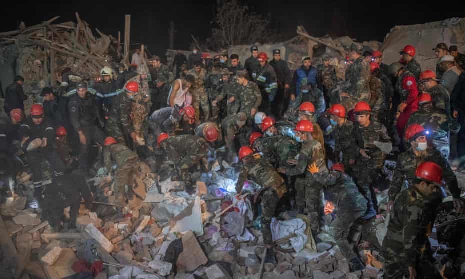 Rescue teams work at a site hit by a strike during fighting over the breakaway region of Nagorno-Karabakh, in the city of Ganja.