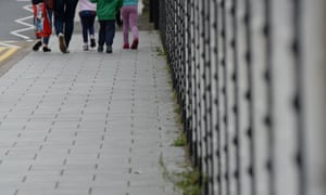 Anonymous children walking down a street