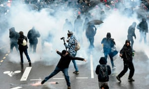 Protesters disperse as tear gas is fired by French police during a demonstration on day 36 of the strike.