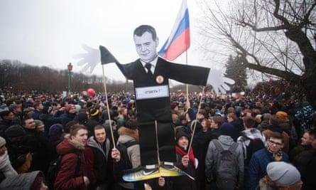 A portrait of Dmitry Medvedev is held aloft during a demonstration in St Petersburg