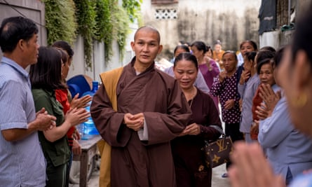 A monk leads family members to prayer in Ha Tinh, Vietnam, after the discovery of 39 bodies in a lorry in Essex.
