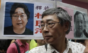 In this June 2016 photo, freed Hong Kong bookseller Lam Wing-kee stands next to a placard with picture of missing bookseller Gui Minhai.