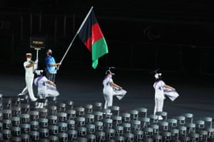 A volunteer carries the Afghanistan flag during the parade.