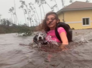 Julia Aylen wades through waist-deep water carrying her pet dog as she is rescued from her flooded home during Hurricane Dorian in Freeport, Bahamas, on Tuesday.