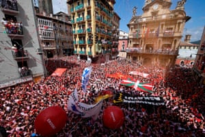 Participants hold red scarves in front of Pamplona's town hall