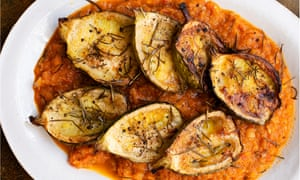 An oval white plate with slices of roast courgette on a bed of tomato sauce