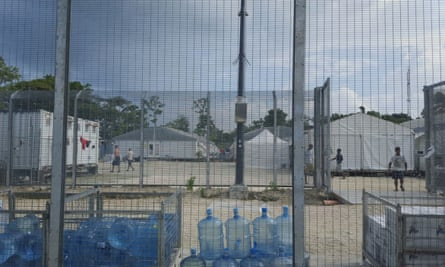 Detainees walk around the compound among water bottles inside the Manus Island detention centre.
