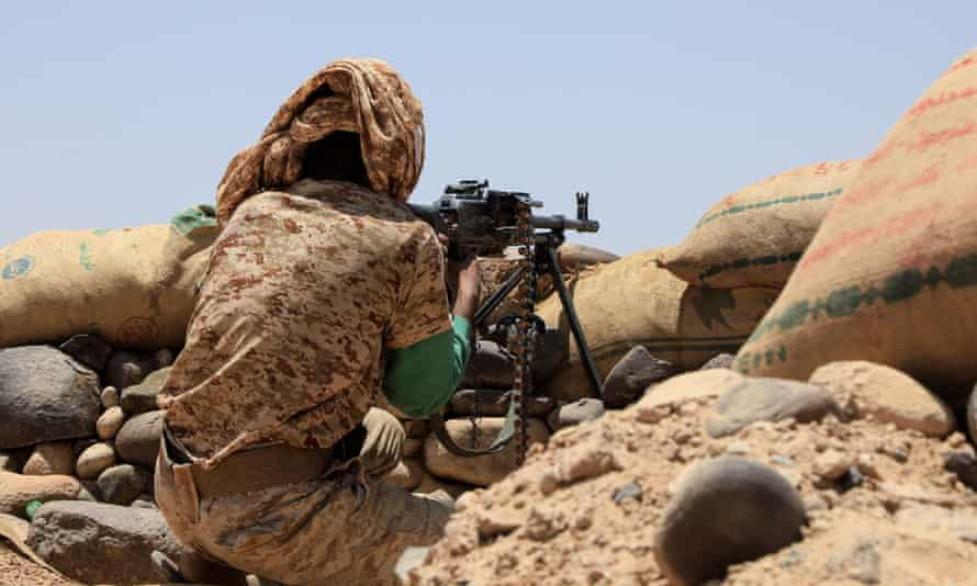 A fighter with forces loyal to Yemen's Saudi-backed government holds a position against Houthi rebels in the north-eastern province of Marib