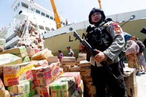 A policeman stands as he secures the transfer of food and aid for victims.