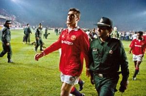 Eric Cantona est escorté hors du terrain par un policier après avoir été envoyé à Manchester United à Galatasaray en 1993.