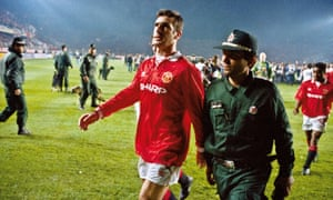 """Images From The Book """"In The Moment' - By Tom Jenkins<br>Manchester United player Eric Cantona is escorted from the pitch by a policeman after he was sent off at the end of the Champions League second round match with Galatasaray at the Ali Sami Yen stadium, Istanbul on November 3rd 1993 (Photo by Tom Jenkins/Getty Images). An image from the book """"In The Moment"""" published June 2012"""