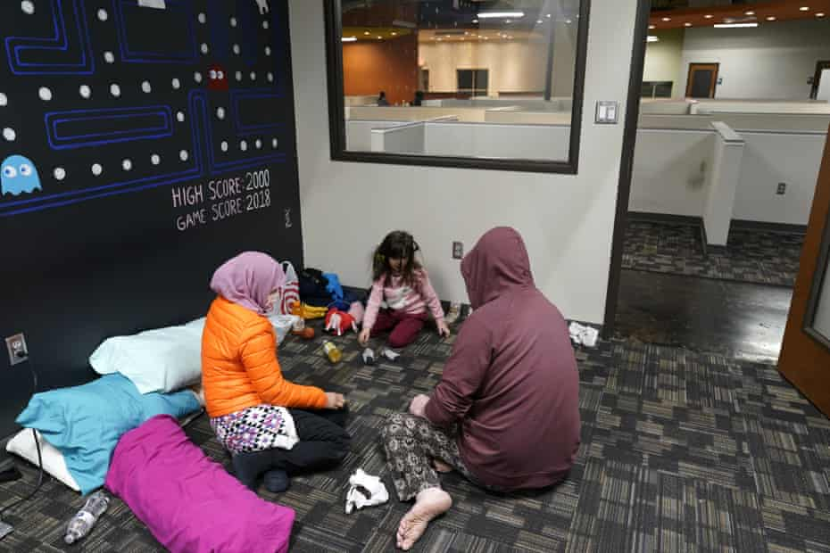 Novi Harris, left, her husband, Christopher, right, and their daughter, Keeva, occupy an office suite at a pop-up warming center in Richardson, Texas, on Tuesday.