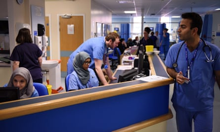 Clinical staff work at computers an NHS England hospital.