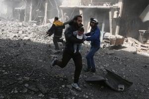 A man carries an injured child