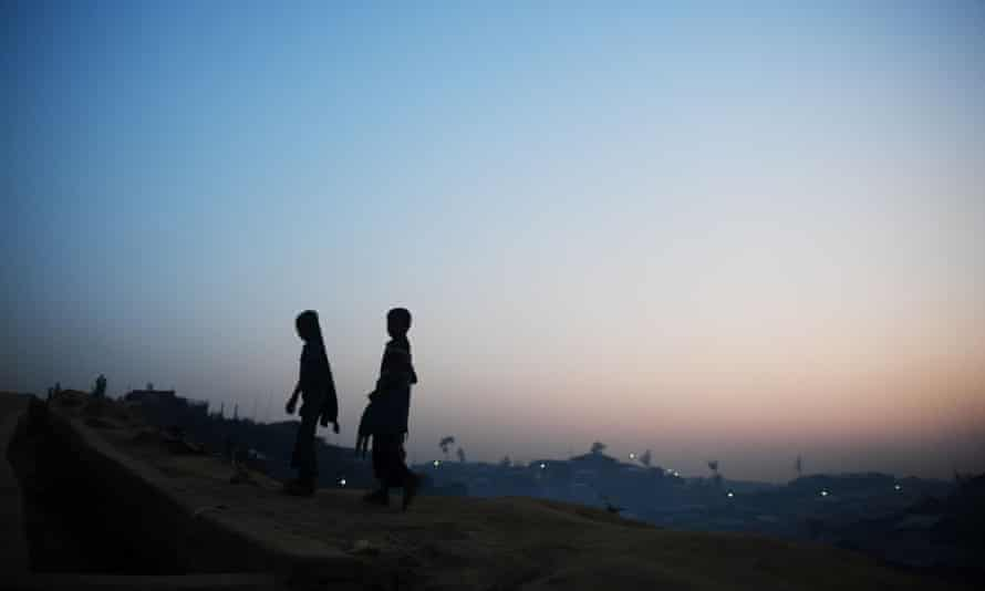 Rohingya refugees walk back to their tent during dusk at the Kutupalong refugee camp