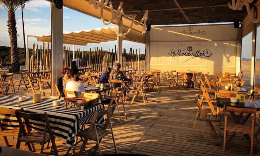 El Maravillas bar at sunset, a few drinkers at tables.