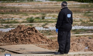 A Misakim charity volunteer standing beside new graves at Rainsough Jewish cemetery in north Manchester last month.