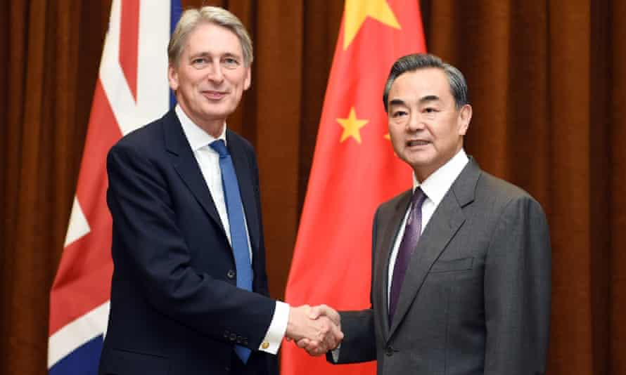 China's foreign minister Wang Yi shakes hands with British foreign secretary Philip Hammond