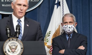 Mike Pence speaks at Friday's press briefing while Dr Anthony Fauci watches. Pence did not wear a mask at the news conference.