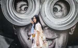 Three young women walk in front of a street mural on a street in Bangkok
