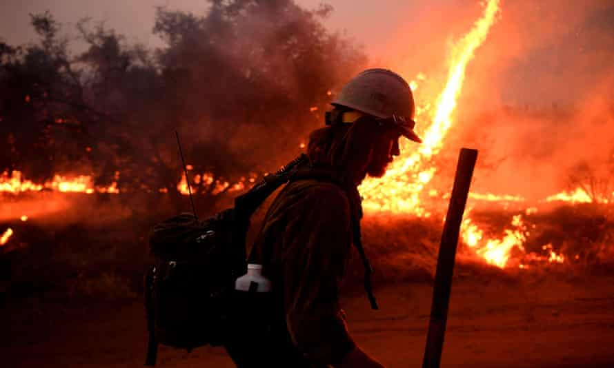 A firefighter in full gear with a helmet and backpack is semi-silhouetted against flames from the El Dorado fire.