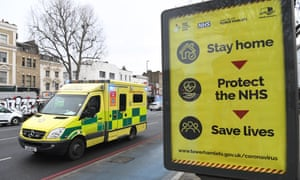 an ambulance speeds past a Covid warning sign