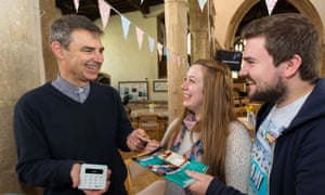 Martyn Taylor, Rector at St George's Church in Stamford, Lincolnshire holding a contactless payment device