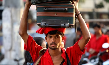 A porter carries bags at Pune train station