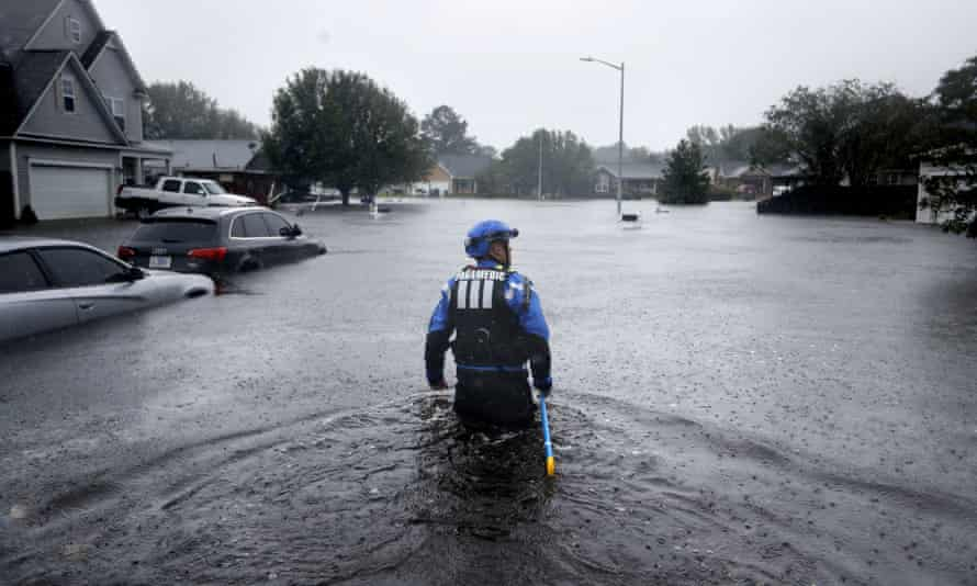 A search and rescue worker wades through a flooded neighborhood in Fayetteville, North Carolina.